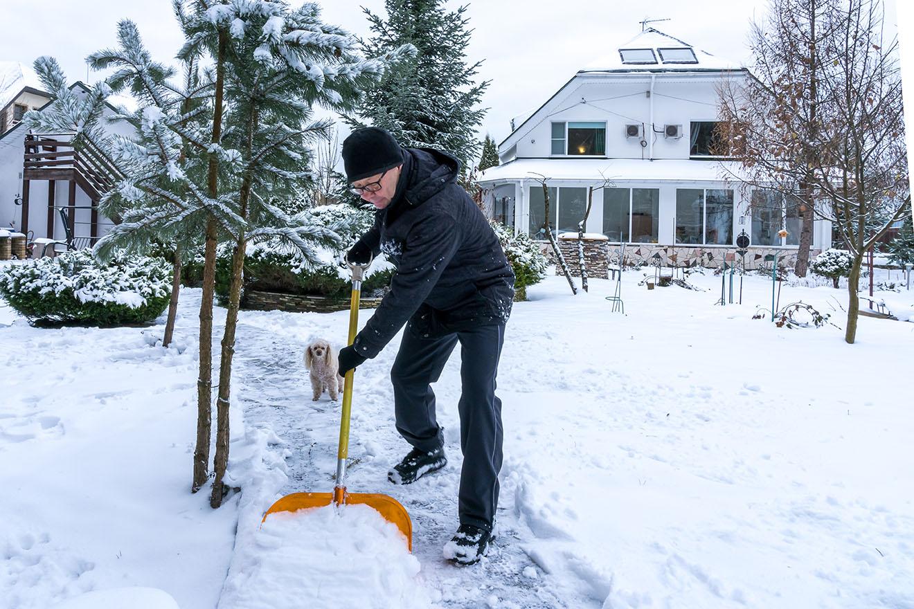 man maakt pad sneeuwvrij