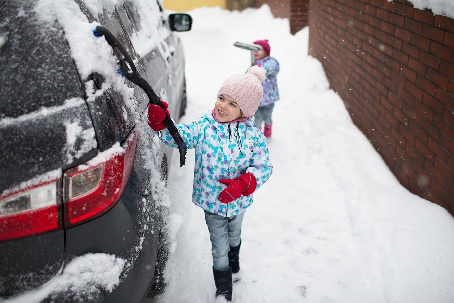klein meisje maakt auto sneeuwvrij